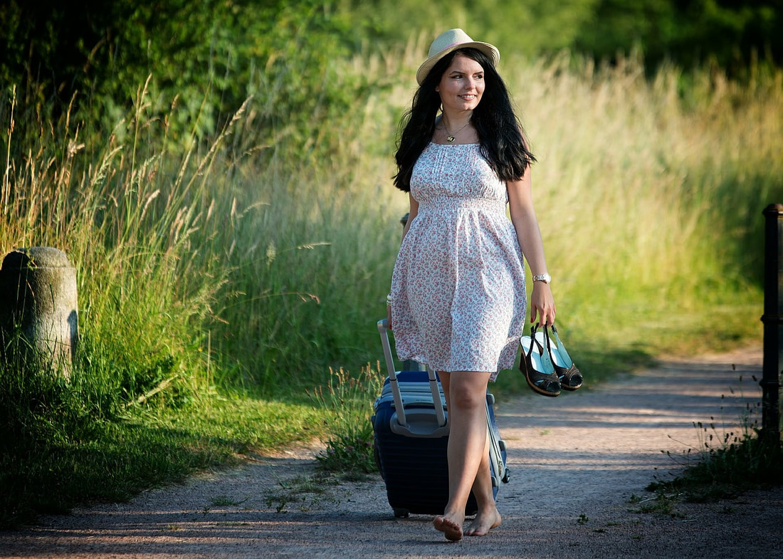 Woman walking down path with suitcase